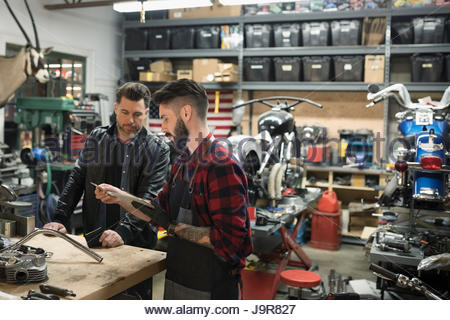 Motorcycle mechanics examining parts in auto repair shop - Stock Photo