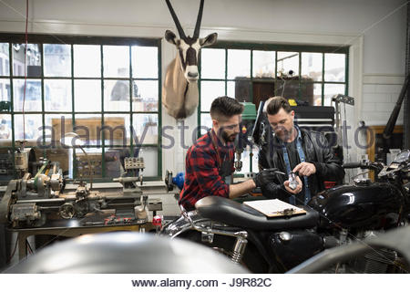 Motorcycle mechanics with clipboard examining part, fixing motorcycle in auto repair shop - Stock Photo