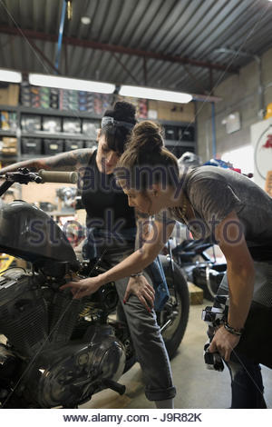 Female motorcycle mechanics talking, fixing motorcycle in auto repair shop - Stock Photo