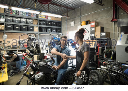 Male customer on motorcycle shaking hands with female mechanic in auto repair shop - Stock Photo