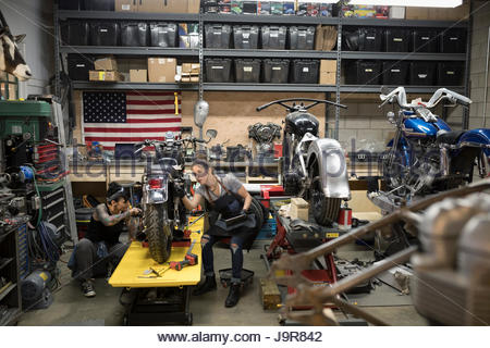 Female motorcycle mechanics fixing motorcycle in auto repair shop - Stock Photo