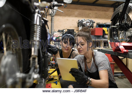 female motorcycle mechanics with digital tablet fixing motorcycle in auto repair shop stock photo