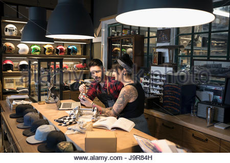 Motorcycle mechanic shop owners examining parts behind counter - Stock Photo
