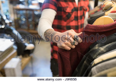 Male customer with tattoo and rings shopping, browsing at clothing in shop - Stock Photo