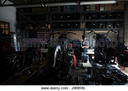 Pensive female motorcycle mechanic working behind motorcycles in auto repair shop - Stock Photo
