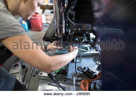 Female auto mechanic fixing motorcycle in auto repair shop - Stock Photo
