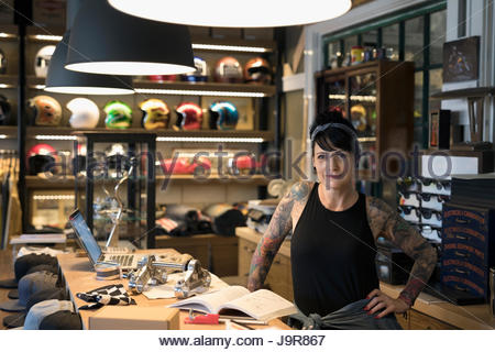 Portrait confident female motorcycle mechanic behind shop counter - Stock Photo