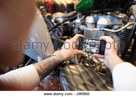 Personal perspective motorcycle mechanic with camera phone photographing engine - Stock Photo