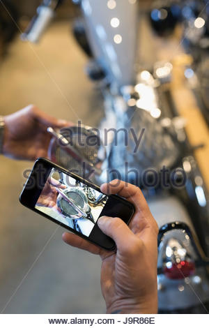 Personal perspective motorcycle mechanic with camera phone photographing part - Stock Photo