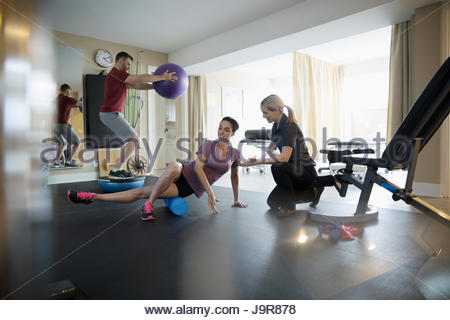 Female physiotherapist working with clients exercising and stretching in clinic gym - Stock Photo