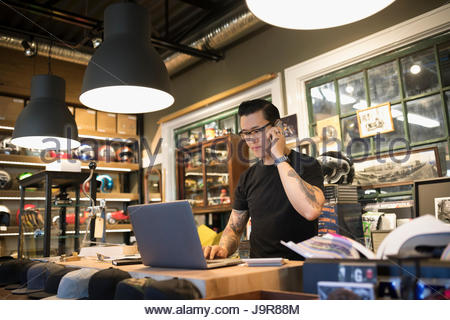 Motorcycle shop owner working at laptop and talking on cell phone behind counter - Stock Photo