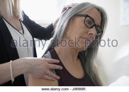 Female physiotherapist stretching neck of client in clinic examination room - Stock Photo
