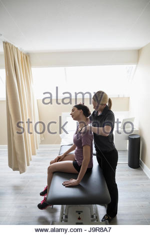 Female physiotherapist stretching neck of client on clinic examination table - Stock Photo