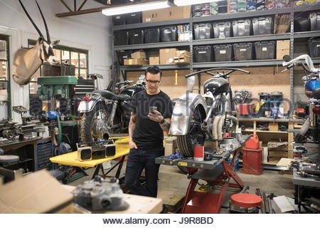 Motorcycle mechanic texting with cell phone in auto repair shop - Stock Photo