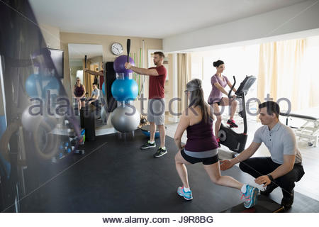 Male physiotherapist guiding clients stretching and exercising in clinic gym - Stock Photo