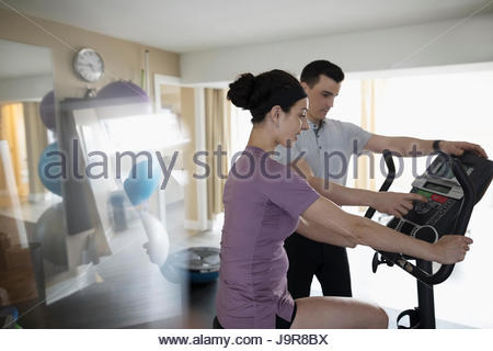 Male physiotherapist guiding female client exercising on exercise bicycle in clinic gym - Stock Photo