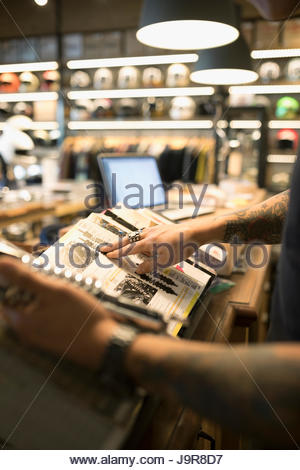 Motorcycle mechanic holding part and browsing catalog in auto repair shop - Stock Photo
