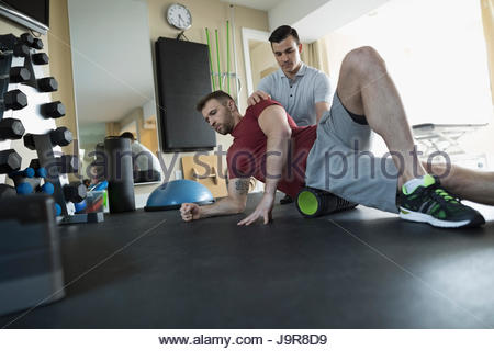 Male physiotherapist guiding client stretching in clinic gym - Stock Photo