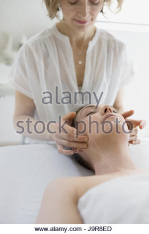 Serene woman receiving face massage on spa massage table - Stock Photo