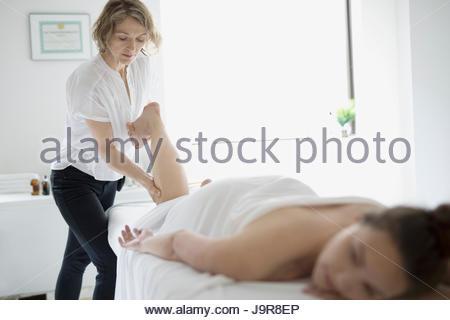 Masseuse massaging leg of woman on spa massage table - Stock Photo