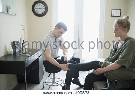 Male physiotherapist examining ankle of woman in clinic examination room - Stock Photo