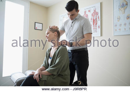 Male physiotherapist examining neck of woman in clinic examination room - Stock Photo