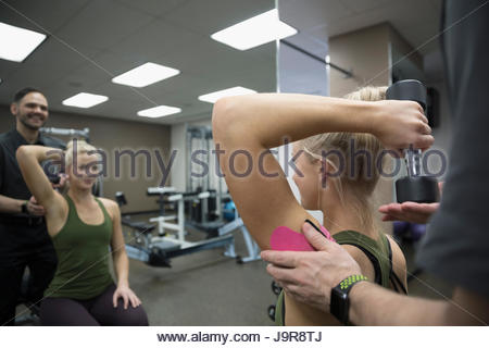 Male physiotherapist helping female client exercising with dumbbell in clinic gym - Stock Photo