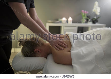 Woman receiving massage on spa massage table - Stock Photo