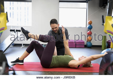 Male physiotherapist helping female client stretching in clinic gym - Stock Photo