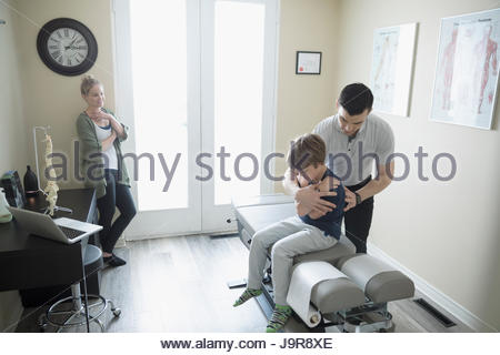 Mother watching male physiotherapist stretching son on clinic examination table - Stock Photo