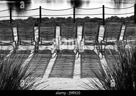 Chairs lined up in a beach against the sunlight and with its shadows being projected on the ground - Stock Photo