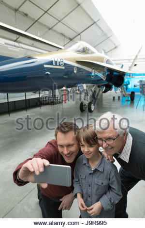 Male multi-generation family with camera phone taking selfie at Air Force jet exhibit in war museum hangar - Stock Photo