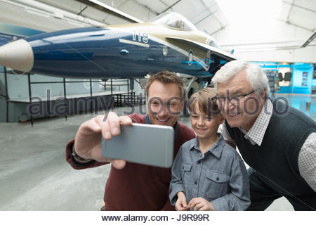 Male multi-generation family taking selfie with camera phone at Air Force jet exhibit in war museum hangar - Stock Photo
