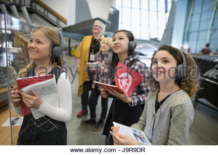 Smiling, curious students wearing headphones and taking notes at exhibit on field trip in war museum - Stock Photo