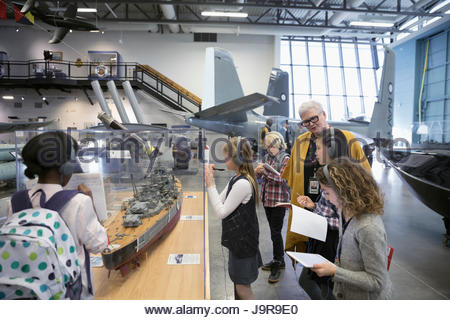 Docent helping students wearing headphones and taking notes at exhibit on field trip in war museum - Stock Photo