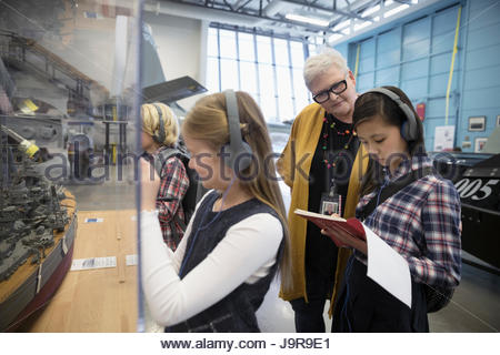 Docent helping students wearing headphones and taking notes on field trip in war museum - Stock Photo