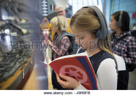 Focused girl student wearing headphones and taking notes at exhibit on field trip in war museum - Stock Photo