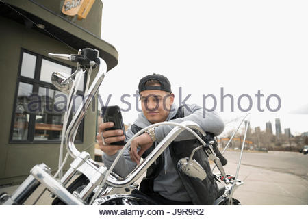 Male biker texting with cell phone on motorcycle in parking lot - Stock Photo