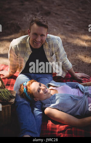 High angle portrait of smiling couple resting on field at farm - Stock Photo