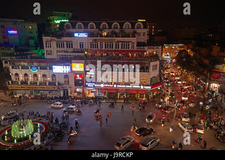 Crazy traffic at night at busy intersection by Hoan Kiem Lake and Old Quarter, Hanoi, Vietnam - Stock Photo