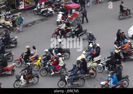 Crazy traffic at busy intersection by Hoan Kiem Lake and Old Quarter, Hanoi, Vietnam - Stock Photo