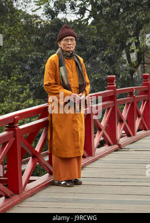 Monk on the Huc Bridge, Hoan Kiem Lake, Hanoi, Vietnam - Stock Photo