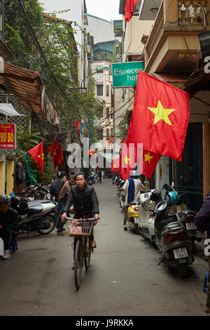 Busy alley and Vietnamese flags in busy Old Quarter, Hanoi, Vietnam - Stock Photo