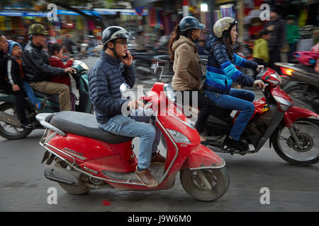 Man on cellphone riding scooter on busy streets, Old Quarter, Hanoi, Vietnam - Stock Photo