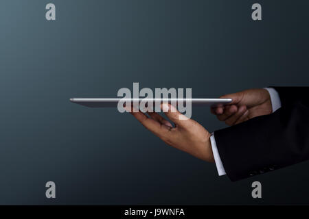 Part of Businessman Hand holding a digital tablet for present modern business work, Side view, Dark tone - Stock Photo