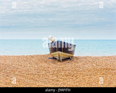 Wooden rowing boat used by local fishermen pulled up on to Bognor Regis beach. - Stock Photo