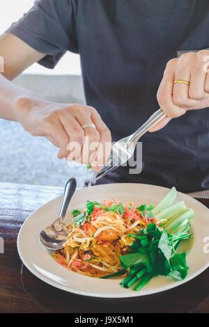 Squeezing lemon on padthai - Stock Photo