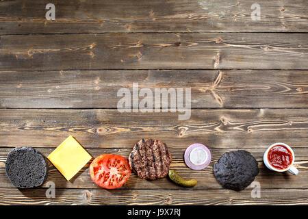 Dark restaurant menu, burger ingredients and copy space. black bun for Burgers. top view. - Stock Photo