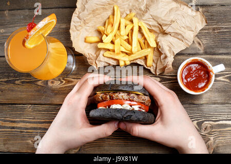 Hands holding fresh delicious burgers with french fries, sauce and fresh orange juice or alcoholic cocktail on the - Stock Photo