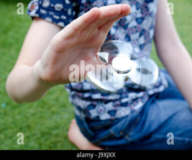 A child playing with a spinning fidget spinner in the garden - Stock Photo